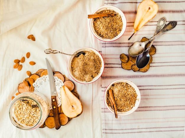 Nahaufnahme einer portion dessert birnenstreuselkuchen in einer roten schüssel auf einer leinentischdecke.