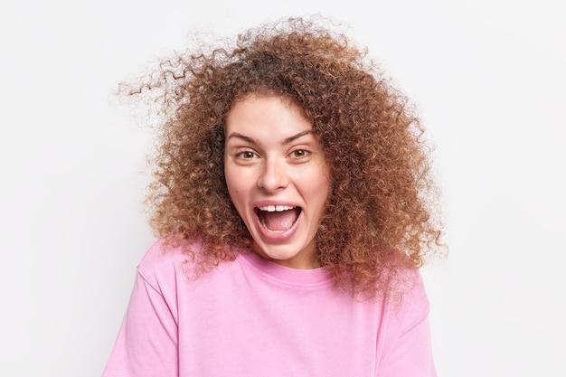 Nahaufnahme einer positiven jungen europäischen frau, die glücklich aussieht, sagt wow, als sie etwas unglaubliches sieht, das in einem lässigen pullover isoliert über einer weißen wand gekleidet ist, hat spaß. emotionen konzept