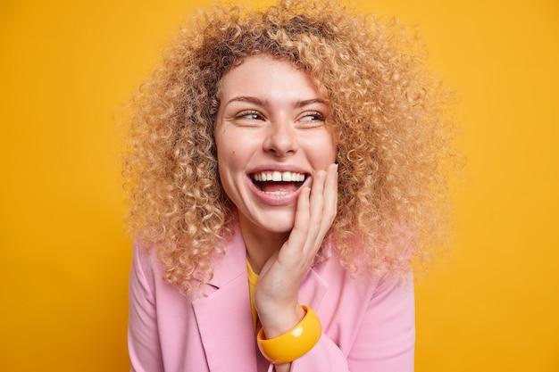 Nahaufnahme einer positiven, lockigen frau, die breit lächelt und die hand auf dem gesicht hält, fühlt sich sehr glücklich, wenn sie von jemandem amüsiert wird, der formelle kleidung isoliert über gelber wand trägt emotionen konzept