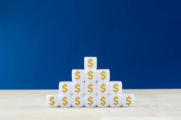Nahaufnahme einer pyramide der weißen würfel mit dollarzeichen auf ihnen. konzept der finanzplanung