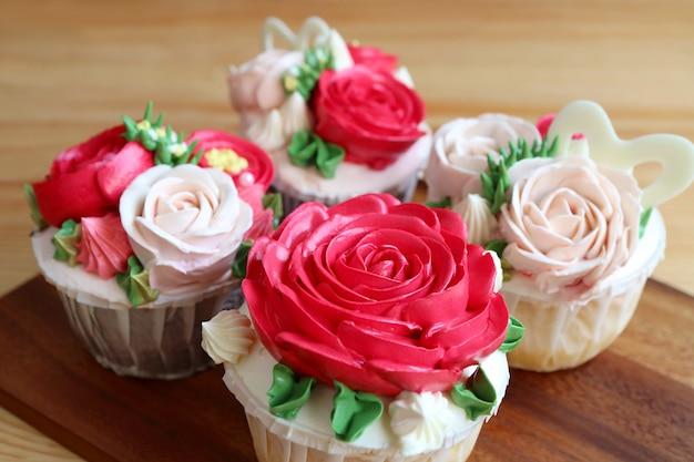 Nahaufnahme einer reihe von wunderschönen rosafarbenen zuckerguss-cupcakes mit selektivem fokus