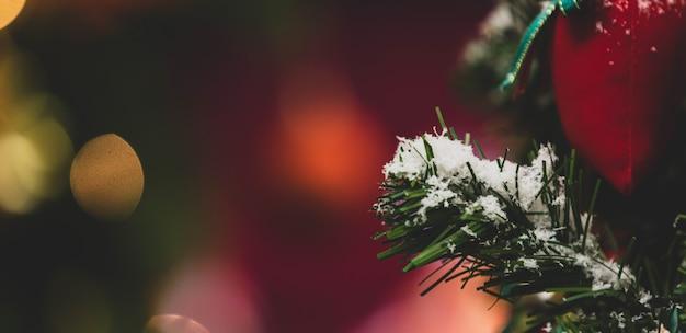 Nahaufnahme einer roten geschenktüte, die mit kunstschnee auf grünem weihnachtskieferzweig und blättern in der traditionellen festnachtsveranstaltung am weihnachtsabend im wohnzimmer hängt.