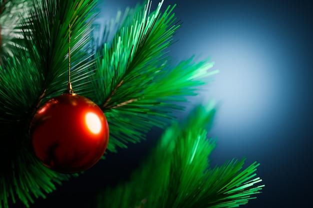 Nahaufnahme einer roten glänzenden weihnachtskugel, die an einem weihnachtsbaum im hintergrund hängt