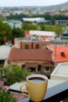 Nahaufnahme einer schale heißen kaffees auf dem balkon mit undeutlicher stadt-ansicht in den hintergrund