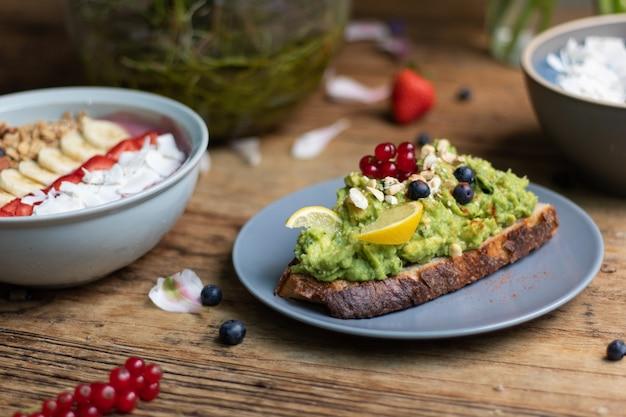 Nahaufnahme einer scheibe schwarzbrot mit avocado-nudeln und einer smoothie-schüssel