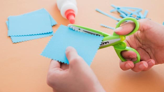 Nahaufnahme einer schere, die das blaue papier auf farbigem hintergrund schneidet