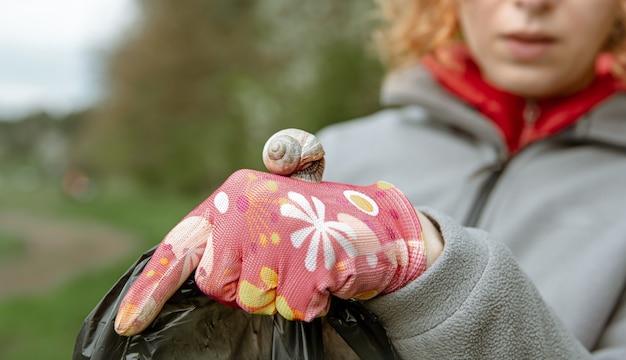 Nahaufnahme einer schnecke auf einem handschuh für die müllabfuhr, die die umwelt säubert.