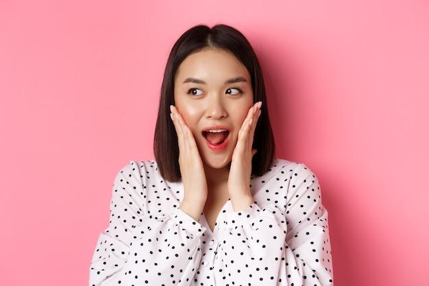 Nahaufnahme einer schönen asiatischen frau, die überrascht und aufgeregt aussieht, hört erstaunliche nachrichten nach links und...