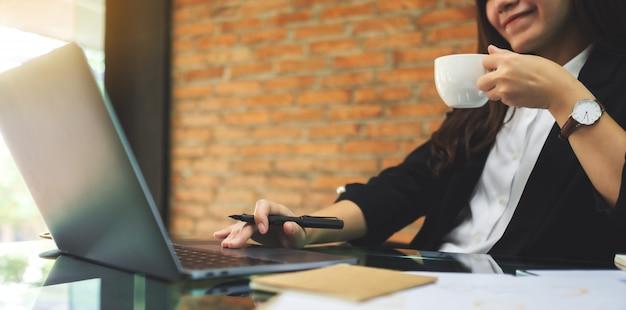 Nahaufnahme einer schönen asiatischen geschäftsfrau, die kaffee trinkt, während sie laptop-computer im büro benutzt und arbeitet