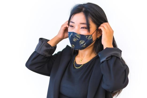 Nahaufnahme einer schönen chinesin, die eine gemusterte gesichtsmaske vor einer weißen wand trägt