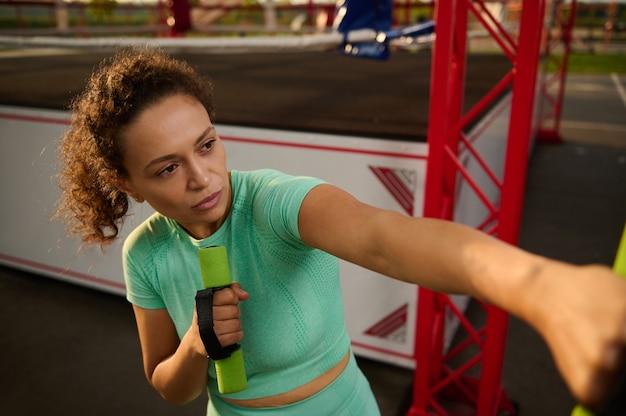 Nahaufnahme einer schönen, entschlossenen sportlichen frau in bewegung, die auf dem sportplatz trainiert, mit kleinen hanteln boxt, ein cardio-training durchführt