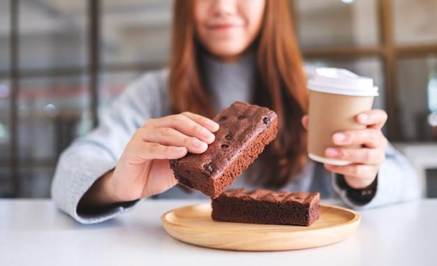 Nahaufnahme einer schönen frau, die ein stück brownie-kuchen hält und isst, während sie kaffee trinkt