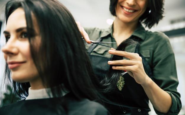 Nahaufnahme einer schönen frau, die sich von einem fachmann im schönheitssalon die haare schneiden lässt.