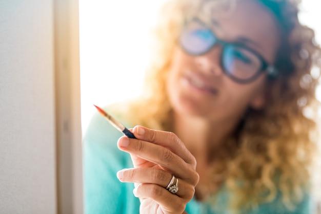 Nahaufnahme einer schönen frau mit brille, die zu hause ein großes blatt malt