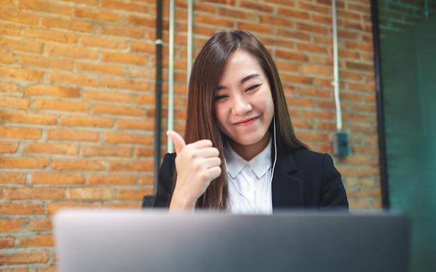 Nahaufnahme einer schönen geschäftsfrau, die schlag oben zeigt, während kopfhörer für videokonferenz auf laptop-computer verwendet wird, online-konzept arbeitend