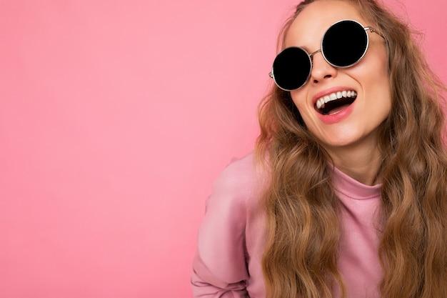 Nahaufnahme einer schönen, glücklichen jungen dunkelblonden, lockigen frau, die über rosafarbener hintergrundwand isoliert ist und lässige rosa sportkleidung und eine stilvolle sonnenbrille mit blick auf die kamera trägt. platz kopieren