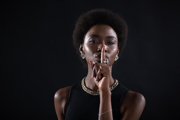 Nahaufnahme einer schönen jungen afroamerikanischen dunkelhäutigen frau mit dem finger auf den lippen, die eine stille geste auf schwarzem hintergrund zeigt