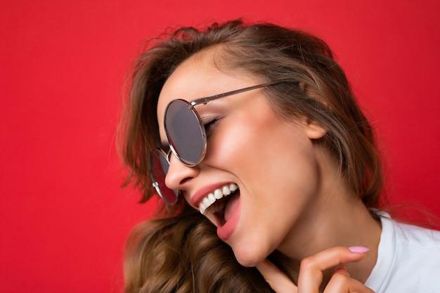 Nahaufnahme einer schönen, positiv lachenden jungen blonden frau, die freizeitkleidung und eine stilvolle sonnenbrille trägt, die auf buntem hintergrund isoliert ist und zur seite schaut