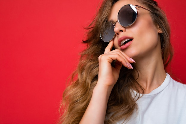 Nahaufnahme einer schönen sexy nachdenklichen jungen dunkelblonden, lockigen frau, die über einer roten hintergrundwand isoliert ist und ein lässiges weißes t-shirt und eine stilvolle sonnenbrille trägt, die nach oben schaut und denkt