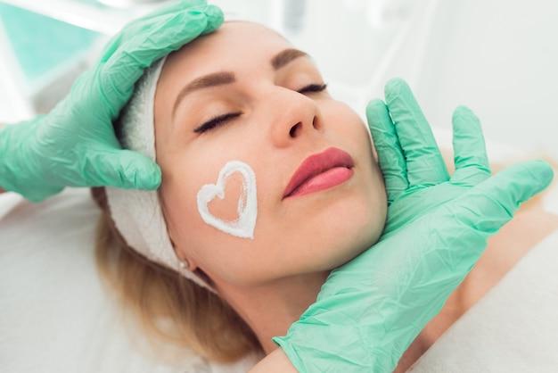 Nahaufnahme einer schönheitstherapeutin, die einer kundin eine gesichtsmaske anwendet