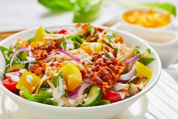 Nahaufnahme einer schüssel huhn club salat mit gebratenem speck, römersalat zerkleinerte hühnerbrust, cheddar-käse, tomaten und joghurt dressing in einer weißen schüssel auf einem holztisch