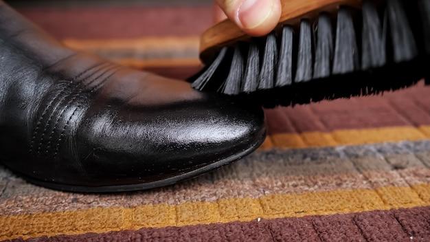 Nahaufnahme einer schuhbürste reibt einen schwarzen lederstiefel