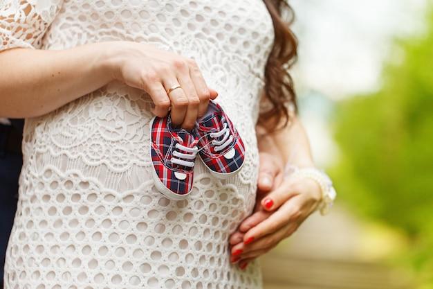 Nahaufnahme einer schwangeren frau und ihres ehemanns, die babyschuhe halten