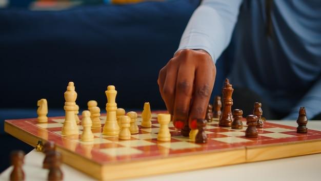 Nahaufnahme einer schwarzen frau, die schachfiguren an bord bewegt und freizeit mit freunden verbringt. gruppe von menschen, die spaß im wohnzimmer haben, sich beim spielen von brettspielen entspannen, verschiedene frauen, die den wettbewerb genießen