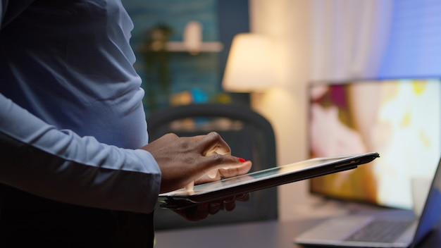 Nahaufnahme einer schwarzen frau mit tablet, surfen, tippen, spät in der nacht im wohnzimmer stehen und eine pause machen. afrikanischer freiberufler, der moderne drahtlose netzwerktechnologie verwendet, um überstunden zu machen