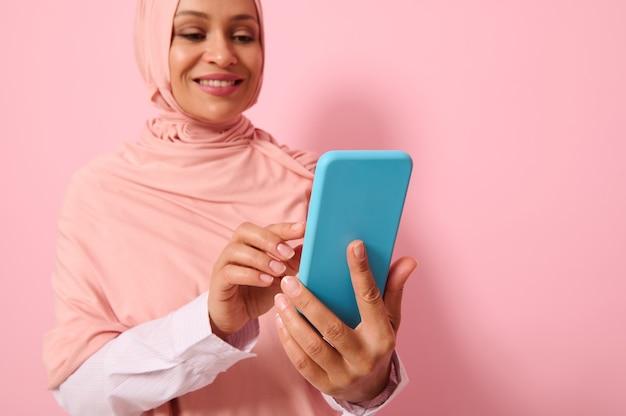 Nahaufnahme einer selbstbewussten arabisch-muslimischen frau mittleren alters in strengem religiösem outfit und bedecktem kopf in rosa hijab, die eine nachricht auf einem mobiltelefon in ihren händen schreibt, farbiger hintergrund, kopierraum