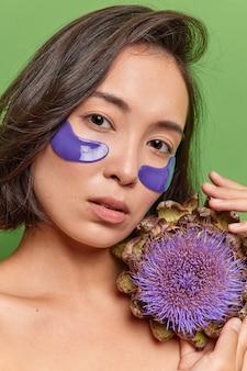 Nahaufnahme einer selbstbewussten ernsthaften asiatischen frau mit dunklem haar, gesunde haut verwendet naturkosmetikprodukte aus blumen, trägt blaue hydrogel-patches unter den augen auf, um schwellungen zu reduzieren und feuchtigkeit zu spenden