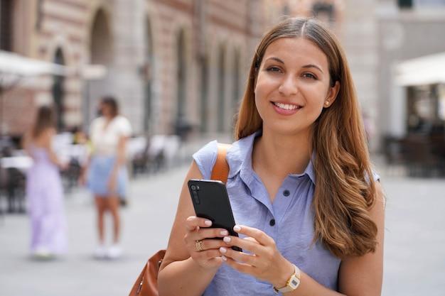 Nahaufnahme einer selbstbewussten jungen dame in trendigem outfit, die ihr handy hält, während sie in der stadtstraße steht und in die kamera schaut