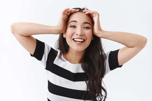 Nahaufnahme einer sorglosen, glücklichen jungen asiatischen frau, die sich erleichtert und entspannt fühlt, einen tollen morgen ohne probleme genießen, optimistisch lächeln, das haar berühren und die kamera fröhlich anstarren