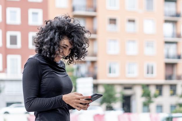 Nahaufnahme einer spanischen frau, die lächelt, während sie ihr telefon benutzt using