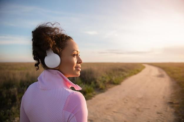 Nahaufnahme einer sportlerin mit kopfhörern, die zur seite schaut, während sie sich nach dem joggen auf einer einsamen landsteppenstraße entspannt