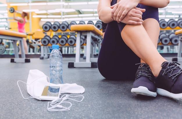Nahaufnahme einer sportlichen frau, die mit hanteln und smartphone im vordergrund auf dem boden des fitnesscenters sitzt.