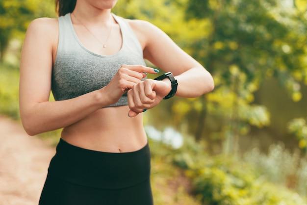 Nahaufnahme einer sportlichen frau mit smartwatch im freien im park bei sonnenuntergang outdoors