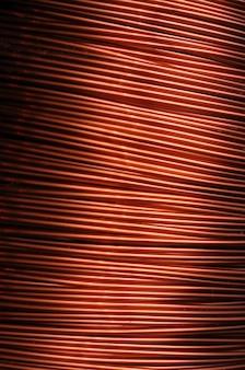 Nahaufnahme einer spule aus rotem kupferdraht bei der herstellung von elektrischen teilen. konzept der elektrogeräte und reparatur. platz für werbung