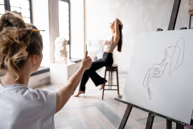 Nahaufnahme einer talentierten frau, die auf leinwand malt