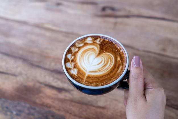 Nahaufnahme einer tasse kaffee lattekunst auf frauenhand im kaffeestubecafé
