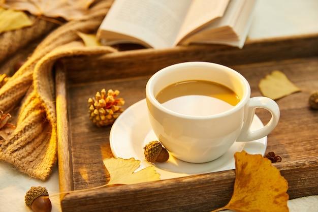 Nahaufnahme einer tasse kaffee und herbstlaub auf holzoberfläche