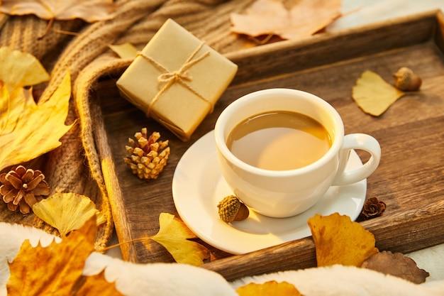 Nahaufnahme einer tasse kaffee und herbstlaub auf holzuntergrund