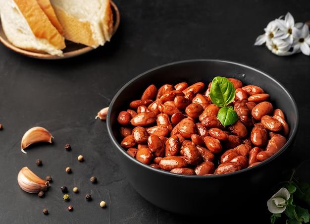 Nahaufnahme einer tasse mit gekochten roten bohnen verziert mit basilikumblättern