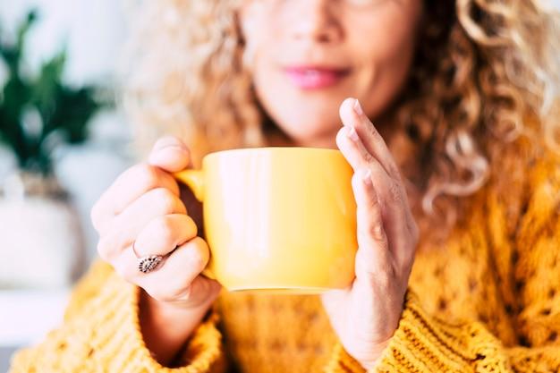 Nahaufnahme einer tasse mit tee- oder kaffeegetränk im inneren und einer schönen defokussierten frau