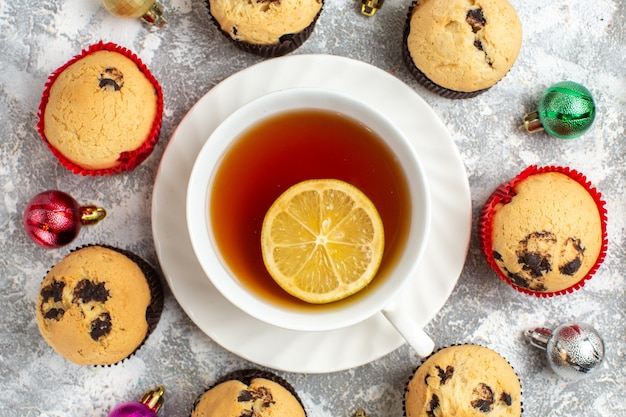 Nahaufnahme einer tasse schwarzen tee mit zitrone unter frisch gebackenen leckeren kleinen cupcakes und dekorationszubehör auf der eisoberfläche