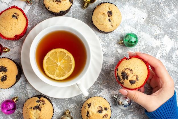 Nahaufnahme einer tasse schwarzen tee mit zitrone unter frisch gebackenen leckeren kleinen cupcakes und dekorationszubehör und hand, die einen kleinen cup cake auf der eisoberfläche hält holding