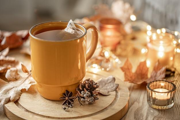 Nahaufnahme einer tasse tee unter den herbstblättern und kerzen auf einem unscharfen hintergrund.