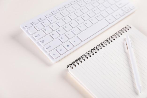 Nahaufnahme einer tastatur und eines notizblocks mit stift auf einem weißen tisch - arbeitskonzept