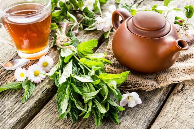 Nahaufnahme einer teekanne und einer tasse tee auf einem holztisch