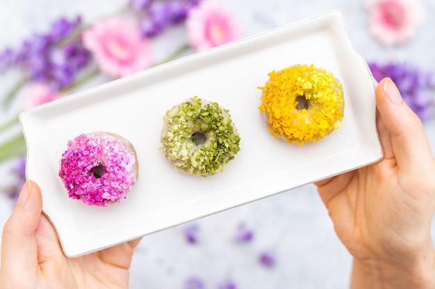 Nahaufnahme einer tischplatte mit veganen rohen bunten donuts